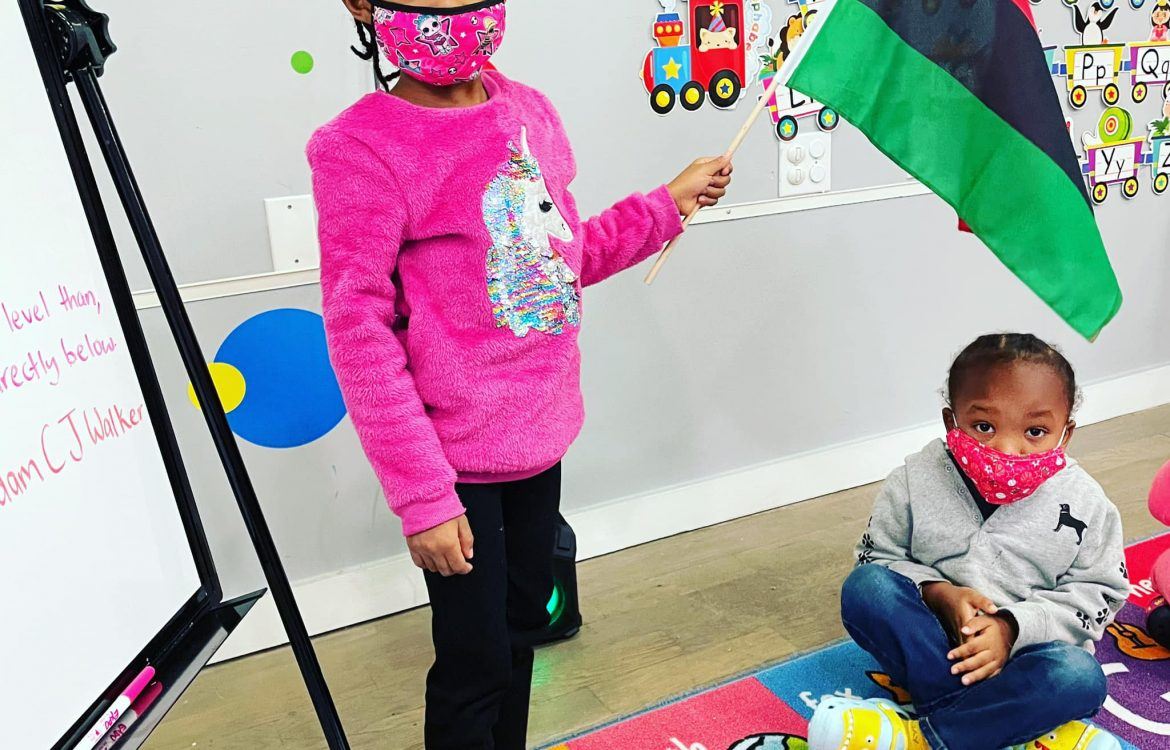 black children in pre-school holding rbg flag