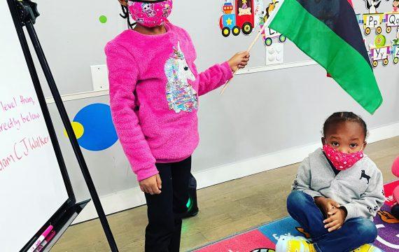 black children in pre-school holding rbg flag